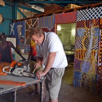 Sail Darwin crew member Paul helps fix the chainsaw at Munupi Arts Centre so that family can go looking for trees to make Pukamani poles from